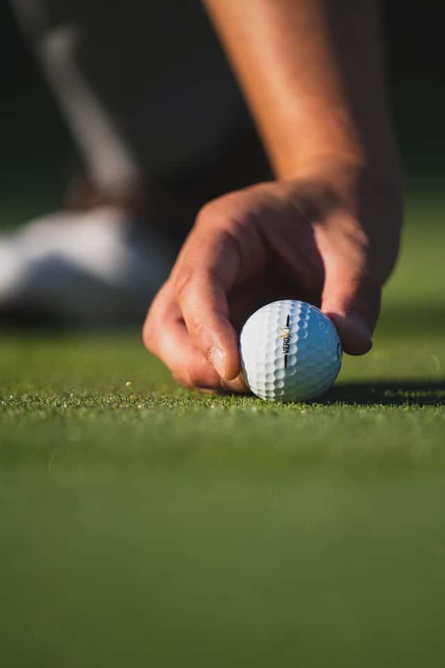 Man placing golf ball on green